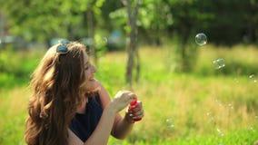 Mãe bonita e sua filha que jogam com bolhas de sabão no parque vídeos de arquivo