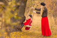 A mãe bonita em um vestido longo está balançando em um balanço que articulado a filha pequena em um revestimento vermelho em um j imagem de stock