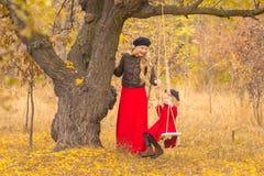 A mãe bonita em um vestido longo está balançando em um balanço que articulado a filha pequena em um revestimento vermelho em um j foto de stock royalty free