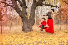 A mãe bonita em um vestido longo está balançando em um balanço que articulado a filha pequena em um revestimento vermelho em um j fotografia de stock
