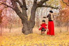A mãe bonita em um vestido longo está balançando em um balanço que articulado a filha pequena em um revestimento vermelho em um j fotos de stock
