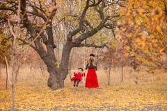 A mãe bonita em um vestido longo está balançando em um balanço que articulado a filha pequena em um revestimento vermelho em um j imagens de stock royalty free