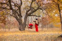 A mãe bonita em um vestido longo está balançando em um balanço que articulado a filha pequena em um revestimento vermelho em um j fotos de stock royalty free