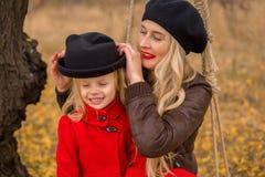 A mãe bonita em um vestido longo está balançando em um balanço que articulado a filha pequena em um revestimento vermelho em um j foto de stock