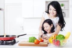 A mãe bonita ensina sua menina cozinhar Imagem de Stock Royalty Free