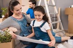 A mãe bonita feliz com filha pequena está considerando o plano para arranjar salas na casa imagem de stock royalty free