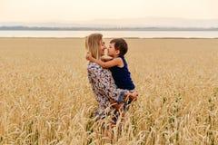 Mãe bonita feliz nova com as caras do bebê no campo de trigo imagem de stock royalty free