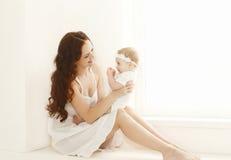 Mãe bonita feliz que joga com bebê bonito em casa fotografia de stock