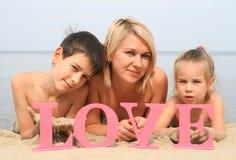 Mãe bonita nova com as crianças que encontram-se na praia com amor da palavra Fotos de Stock Royalty Free