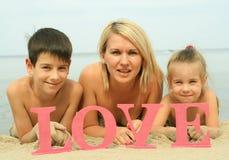 Mãe bonita nova com as crianças que encontram-se na praia com amor da palavra Fotografia de Stock Royalty Free