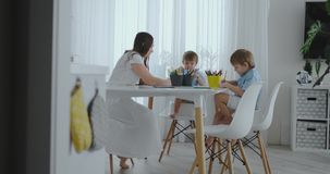 A mãe bonita nova da família feliz e dois filhos tiram com os lápis coloridos que sentam-se na tabela na cozinha E vídeos de arquivo
