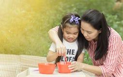 a mãe bonita nova da imagem está alimentando sua menina bonito imagens de stock royalty free