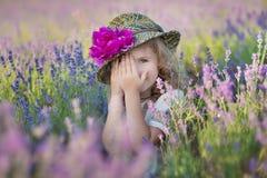 Mãe bonita nova da senhora com a filha bonita que anda no campo da alfazema em um dia do fim de semana em vestidos e em chapéus m Fotografia de Stock
