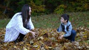 A mãe bonita nova e seu filho pequeno têm o divertimento na floresta que do outono salta e joga as folhas no ar eles filme