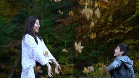 A mãe bonita nova e seu filho pequeno têm o divertimento na floresta que do outono salta e joga as folhas no ar eles vídeos de arquivo