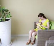 A mãe bonita nova está amamentando o bebê. Imagens de Stock