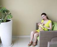 A mãe bonita nova está amamentando o bebê. Imagens de Stock Royalty Free