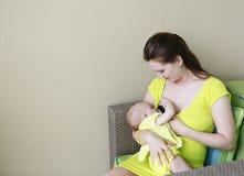 A mãe bonita nova está amamentando o bebê. Fotos de Stock