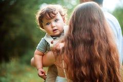 Mãe bonita nova que abraça seu filho pequeno da criança contra a grama verde Mulher feliz com seu bebê em um verão imagem de stock