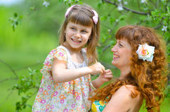 Mãe bonita nova que anda com sua filha no jardim Imagem de Stock Royalty Free