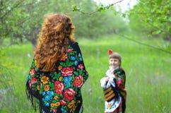 Mãe bonita nova que anda com sua filha no jardim Imagens de Stock