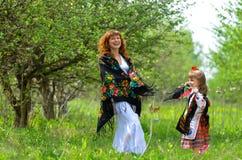 Mãe bonita nova que anda com sua filha no jardim Foto de Stock