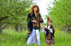 Mãe bonita nova que anda com sua filha no jardim Imagens de Stock Royalty Free