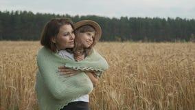 Mãe bonita que abraça sua filha pequena, falando, sorrindo filme