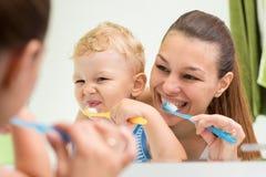 Mãe bonita que ajuda seu filho a escovar os dentes no banheiro imagem de stock