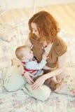 Mãe bonita que amamenta seu infante Imagens de Stock Royalty Free