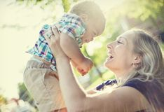 Mãe bonita que guarda seu bebê adorável na luz solar do por do sol imagens de stock royalty free