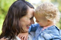 Mãe bonita que ri com bebê Fotografia de Stock Royalty Free