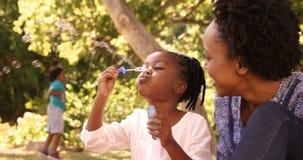 A mãe bonito e a filha estão jogando com bolha em um parque filme