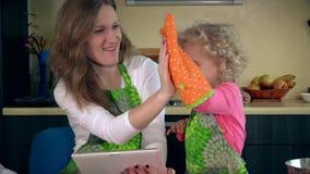 A mãe brincalhão com ajudante pequeno tem o divertimento na cozinha com tablet pc video estoque