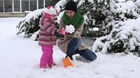 A mãe brincalhão com o castelo entusiasmado da neve da construção da menina da filha e destrói-o vídeos de arquivo