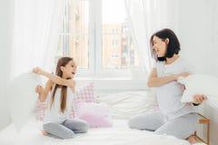 A mãe brincalhão e o daugher têm o divertimento junto, têm a luta de descanso fotografia de stock royalty free