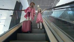 Mãe caucasiano feliz no vestido do verão e sua filha do lettle que vai abaixo da escada rolante no aeroporto filme