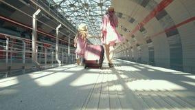 Mãe caucasiano nova com mala de viagem e sua filha pequena que anda na estação de trem video estoque