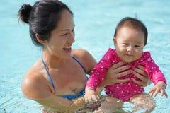 A mãe chinesa asiática que ajuda seu bebê aprende como nadar Fotografia de Stock Royalty Free