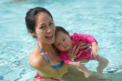 A mãe chinesa asiática que ajuda seu bebê aprende como nadar Fotografia de Stock