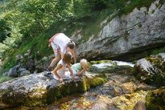 Mãe com água potável das crianças de um córrego puro, fresco e fresco da montanha em uma viagem da família foto de stock royalty free