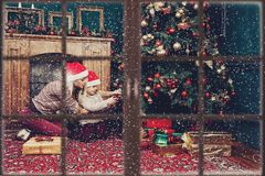 Mãe com a árvore de Natal vestindo da criança antes do ano novo fotos de stock royalty free