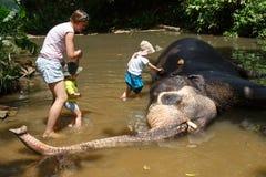 Mãe com as crianças que acariciam o elefante asiático no captiveiro, acorrentado, abusado atraindo turistas foto de stock royalty free