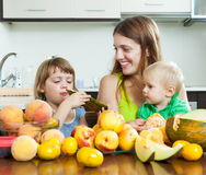 Mãe com as crianças que comem pêssegos Imagens de Stock