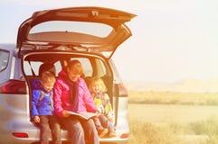 Mãe com as crianças que olham o mapa quando curso pelo carro Foto de Stock Royalty Free