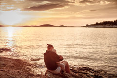 Mãe com as crianças que sentam-se na praia, por do sol de observação Fotos de Stock