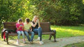 Mãe com as crianças que sentam-se nos smartphones do banco e do móbil do uso filme