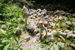Mãe com as crianças que têm o divertimento, jogando por uma angra da montanha no verão fotos de stock