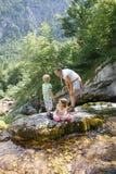 Mãe com as crianças que têm o divertimento, jogando por uma angra da montanha no verão fotografia de stock
