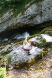 Mãe com as crianças que tomam um selfie, sentando-se em uma rocha por um córrego da montanha em uma viagem da família imagem de stock